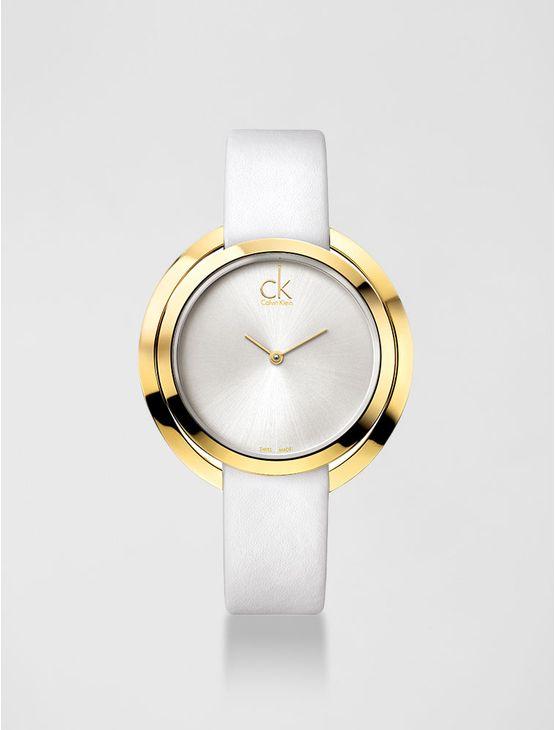 Relógio analógico feminino Calvin Klein com pulseira em couro branco e caixa em aço dourado, vidro em cristal mineral. Resistência à água: 3 BAR. Mecânismo Suíço, função hora e minuto.