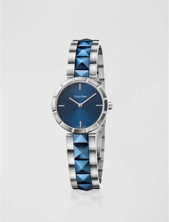 Relógio analógico feminino Calvin Klein com pulseira e caixa em aço misto com azul, vidro em cristal mineral. Resistência à água: 3 BAR. Mecânismo Suíço, função hora e minuto.