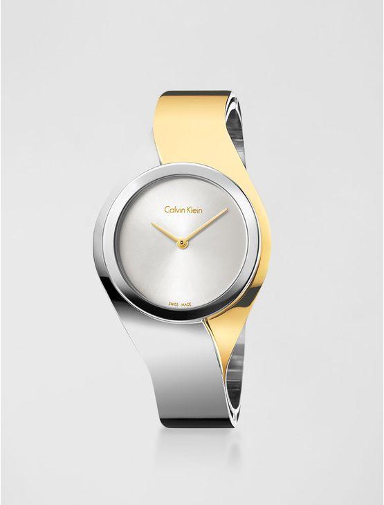 Relógio analógico feminino Calvin Klein com pulseira e caixa em aço misto com dourado, vidro em cristal mineral. Resistência à água: 3 BAR. Mecânismo Suíço, função hora e minuto.